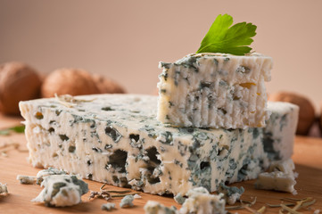 Slice of French Roquefort cheese  with walnuts, copy space.
