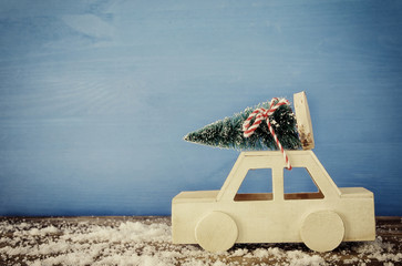 Wooden car carrying a christmas tree on snowy table