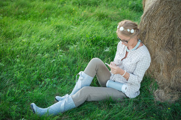 Beautiful young woman listening to the music in the meadow