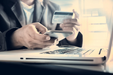 Man's hands holding a credit card and using smart phone for onli