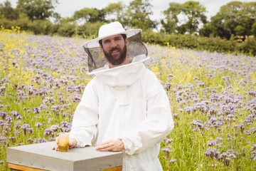 Beekeeper holding a bottle of honey on the beehive