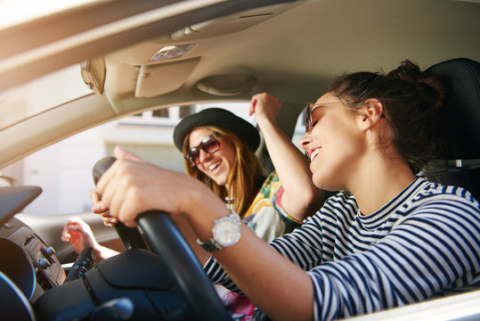 Two young woman singing along in the car