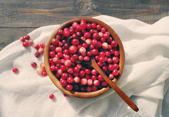 Fresh red forest cranberry in a round bowl with a wooden spoon on white linen fabric on a table surface. Autumn harvest of wild berries