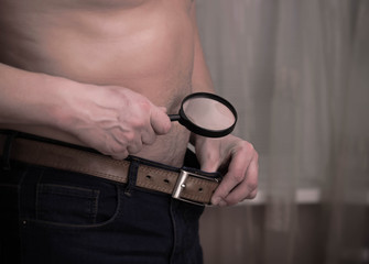 Guy having size worries and checking out with a magnifying glass