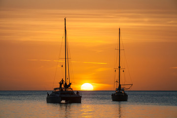Sun setting over ocean, person standing on sailboat in silhouette. Large white sun on horizon in Caribbean. Marigot Bay, St Lucia.