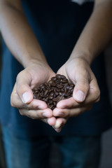 Man holding coffee beans in cupped hands, close-up