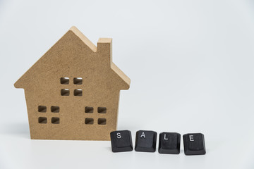 Wooden house toy and SALE word from keyboard with white background and selective focus