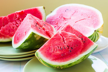 A piece of juicy ripe watermelon with fleshy pink flesh on a lig
