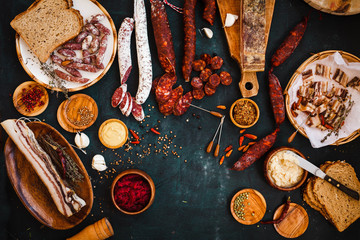 Overhead view of cured meats, sausage with mustard sauce on rustic dark table.