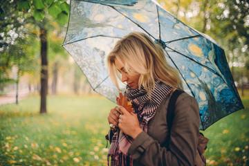Девушка с зонтом гуляет под дождём по осеннему городскому парку
