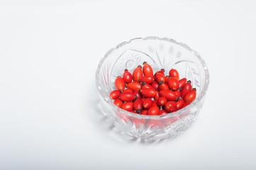 Owoce dzikiej róży w kryształowym szkle.