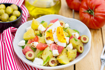 Potato salad with tomato, bell pepper, feta cheese and eggs
