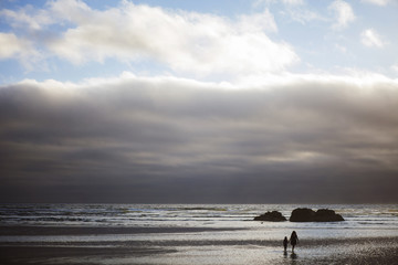 Mother and daughter walking at beach against cloudy sky