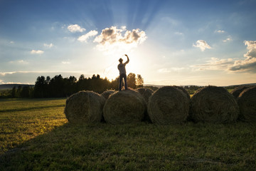 Silhouette cowboy spinning rope while standing on hay bales