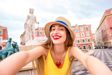 Young female traveler making selfie photo in front of the famous Apollo fountain in Nice city in France