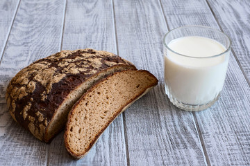 Glass of milk and dark brown bread on the table