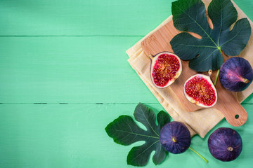 Fresh figs with leaves on green wooden background. Top view.