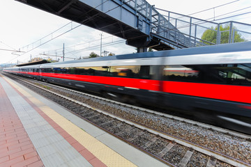 High speed passenger trains on railroad platform in motion. Blur effect of commuter train. Railway station in Florence, Italy. Industrial landscape