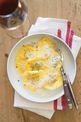Butter and thyme ravioli served with grated parmesan cheese and glass of red wine