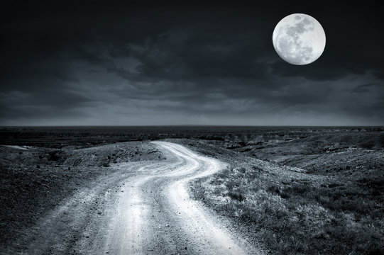 Empty rural road going through prairie at full moon night with dramatic cloudy sky