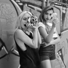 Urban girls have fun with retro vintage photo camera outdoor near grunge wall, black and white image.
