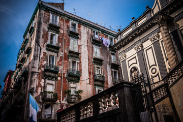 Typical buildings in the oldest part of Naples at the entrance of the famous underground Naples. The flag represents the colors of the football team of the city.