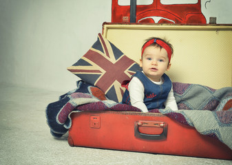 Cute Baby girl sitting in old vintage suitcase