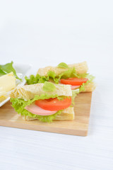 Sandwich with ham, cheese and vegetables. Breakfast or lunch background