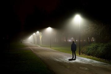 Einsame Person geht auf Straße in der dunklen Nacht
