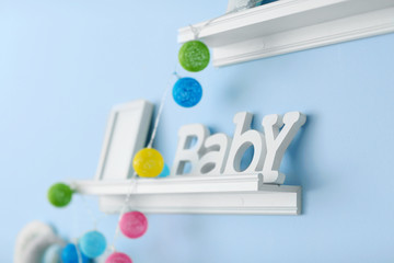 White wooden shelves on blue wall in baby room