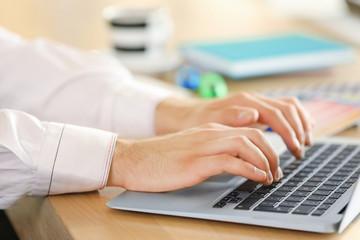 Man typing on laptop in office, closeup