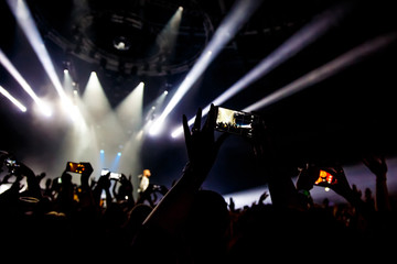 People at concert shooting video or photo by smartphone