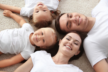 Happy parents with children lying on floor