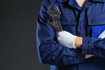 Young mechanic in uniform  and gloves with a wrench standing on a black background.Closeup