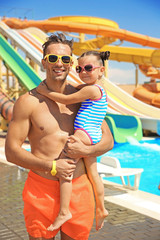 Handsome father with little daughter on blurred water slides background