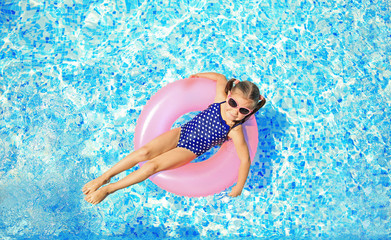 Little girl with pink rubber ring in swimming pool