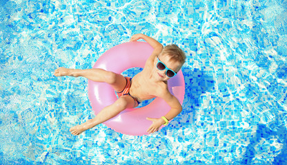 Little boy with pink rubber ring in swimming pool