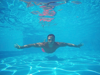 Sporty young man swimming underwater in pool