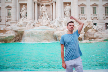 Young man tourist trowing coins at Trevi Fountain, Rome, Italy for good luck. Caucasian guy making a wish to come back.