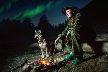 Scout girl with her dog around campfire at night  stars and aurora borealis