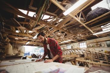 Carpenter looking at blueprint in workshop
