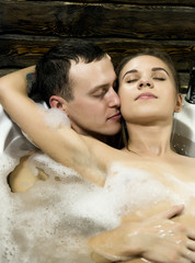 young beautiful couple is enjoying a bath, embrace and kissing. Bubbles and foam