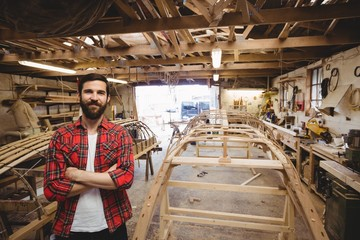 Portrait of man standing near a wooden boat frame
