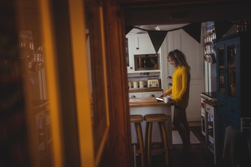 Woman using digital tablet while having coffee in kitchen