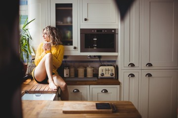 Beautiful woman drinking coffee while sitting in the kitchen