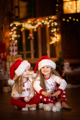 Girls sister friends hugging sitting at  Christmas tree, concept