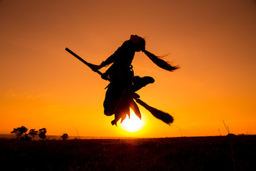 Silhouette of young witch flying on the broomstick