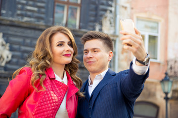 young couple dressed in autumn clothes make selfie on background solar city