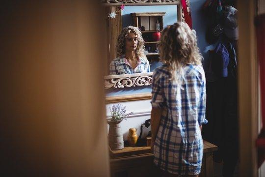 Beautiful woman looking herself in mirror