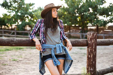 Relaxed woman cowgirl in hat standing and resting on ranch